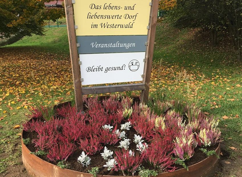 Etzbacher Ortseingangsschild begrüßt mit Blütenpracht