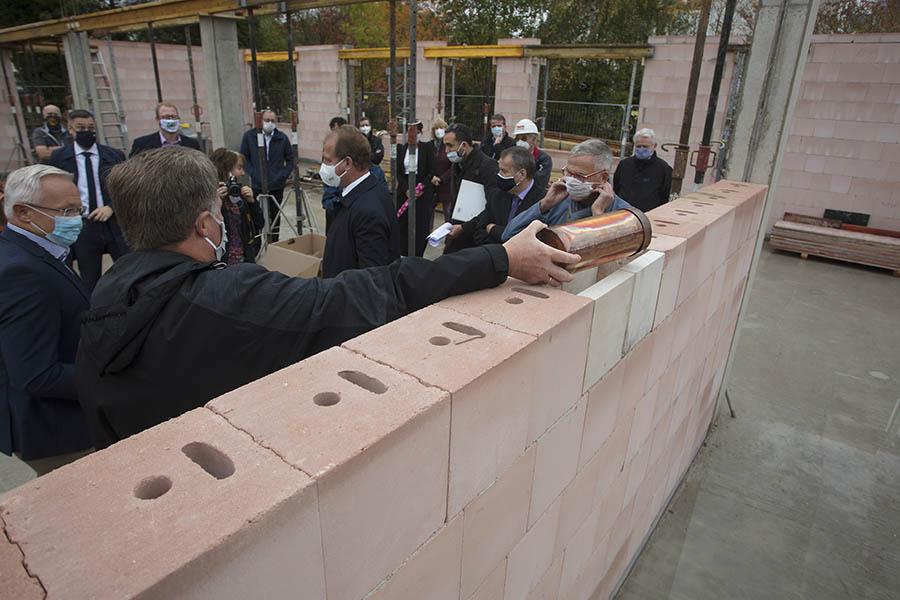 Horst Rasbach legt die Hülse ins Mauerwerk. Darin sind Münzen, eine gedruckte Zeitung und ein DIN A 4 Blatt mit Daten. Fotos: Wolfgang Tischler
