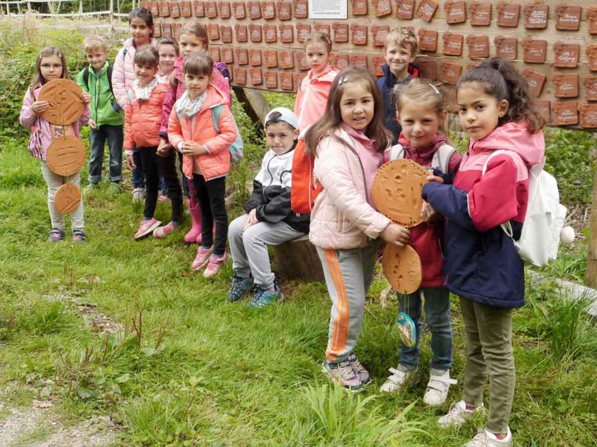 Kinder bringen ihre Kunstwerke in den Wald
