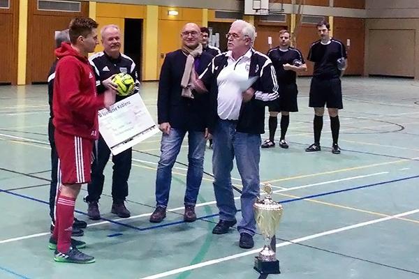 """Der """"Capitano"""" der Spvvg. Lautzert/Oberdreis Alexander Marquardt (links) freut sich über die Glückwünsche des Spielausschussvorsitzenden des FVR, Bernd Schneider (vorne, rechts) und natürlich auch über einen Scheck in Höhe von 400 Euro. Auch der Vizepräsident des Fußballverbandes Rheinland, Alois Reichert (2.v.r.) schloss sich den Glückwünschen an. Foto: Ralf Engel"""