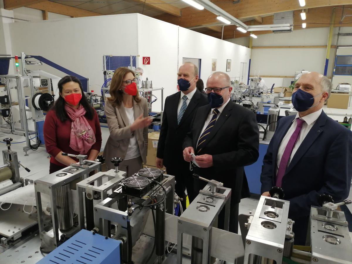 """Wie wird eine FFP2-Maske """"zusammengebaut""""? Wei Hong (links) und Peter Stolfig (Mitte) erläuterten Sabine Bätzing-Lichtenthäler, Dr. Peter Enders und Ottmar Haardt (rechts) den Vorgang. (Foto: vh)"""