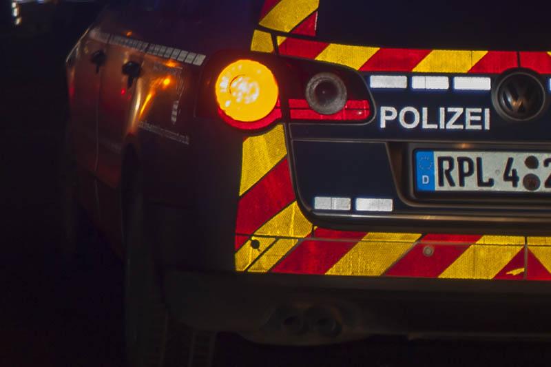 PKW prallt auf Polizeifahrzeug, das Unfallstelle sichert