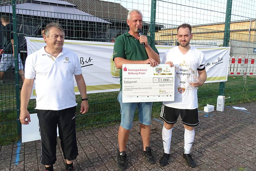 Klaus Robert Reuter (links) und Björn Birk  (Mitte) überreichen dem Pokalsieger SSV Weyerbusch den Prämienscheck der Bitburger Brauerei  über 1.000 Euro. Fotos: Willi Simon
