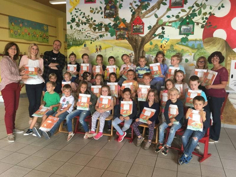 Schulleiterin Elke Ofterdinger, Kim Hoffmann und die Kinder der ersten Klasse mit ihren Lehrern. Foto: Bank