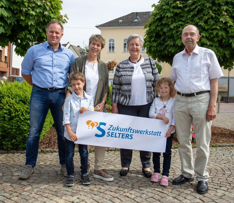 Bildunterschrift: Die Selterser Familie Chmieleck zeigt das Logo der Zukunftswerkstatt. Sie möchten sich mit drei Generationen in den Mitbestimmungsprozess einbringen. Foto: Eckhard Schneider