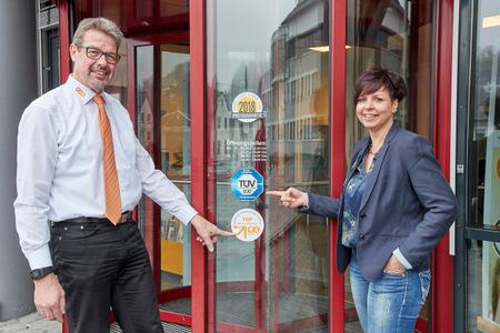Freude über die neuen Auszeichnungen bei Sandra Schattner (rechts) und Mitarbeiter Thomas Kloft vor dem Kundenzentrum in Westerburg. (Foto: evm/Ditscher)