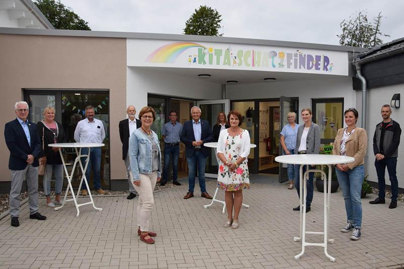 """Ortsbürgermeisterin Anette Wagner (5.v.l.) gemeinsam mit Landrat Achim Hallerbach (7.v.l.), Volker Mendel (1.v.l.), der KiTa-Leiterin Dorothee Dutz (9.v.l.), Bauamtsleiter der VG Markus Sommer (13.v.l.) sowie das Architekten-Team und Mitarbeiterinnen der """"Schatzkiste"""" vor der """"neuen"""" KiTa in Dürrholz. Foto: Kreisverwaltung"""