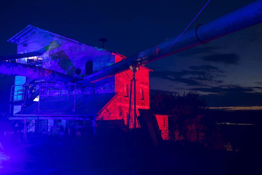 Feuerrot glühende und grau-gelb zerkratzte Industriegebäude